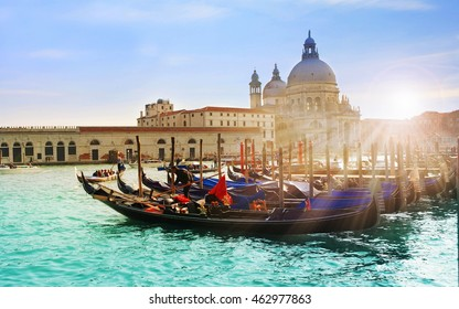 VENEZIA, ITALY  - April 11, 2015: Beautiful view of traditional Gondola on famous Canal Grande with Basilica di Santa Maria della Salute in golden evening light at sunset in Venice, Italy.