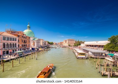 VENEZIA, ITALY – MAY 31, 2019: tourists visiting city while boat passing and waters flowing in Canal Grande, main channel of Venezia, near Saint Lucia Railway Station and Saint Simeon Church