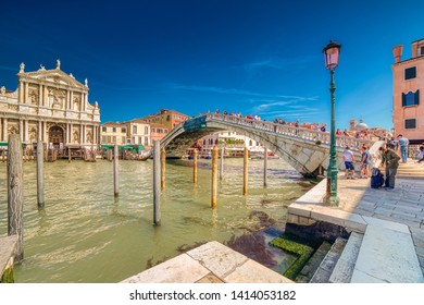 VENEZIA, ITALY – MAY 31, 2019: tourists visiting city while waters flowing in Canal Grande, main channel of Venezia, under Bridge Ponte degli Scalzi near Saint Mary of Nazareth church