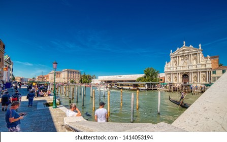 VENEZIA, ITALY – MAY 31, 2019: tourists visiting city while waters flowing in Canal Grande, main channel of Venezia, near Saint Lucia Railway Station and Saint Mary of Nazareth church