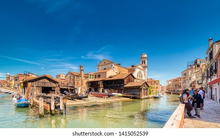 VENEZIA, ITALY – MAY 31, 2019: tourists visiting the city and enjoying the view of  Squero of San Trovaso, typical Venetian boatyard for building gondolas