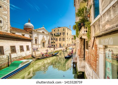 VENEZIA, ITALY – MAY 31, 2019: tourists visiting the city and enjoying ride on gondolas passing in Rio del Mondo Novo typical water channel of Venice