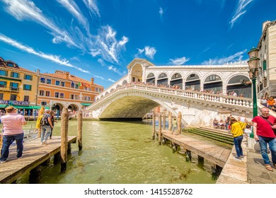VENEZIA, ITALY – MAY 31, 2019: tourists visiting city while waters flowing in Canal Grande, main channel of Venezia, under Rialto Bridge