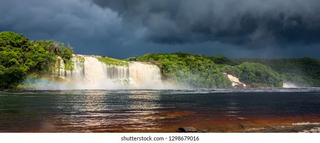 Venezuela. Hacha falls with rainbow in the lagoon of the Canaima national park before the storm - Latin America