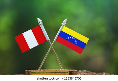 Venezuela and Peru small flag with blur green background
