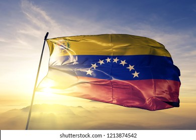 Venezuela Venezuelan Bolivarian republic national flag with coat of arms textile cloth fabric waving on the top sunrise mist fog