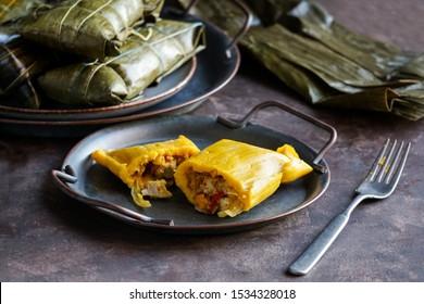 Venezuelan christmas food - hallaca - corn dough stuffed with a stew of pork and chicken and chicken salad, ensalada de gallina