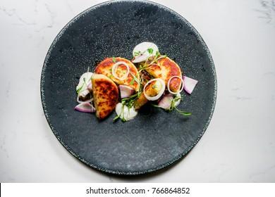 Venezuelan Stuffed Arepas Dish with Onions on a Black Plate