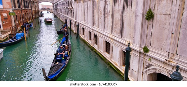 VENICE - APRIL 2014: Famous gondolier along small canal. Approximately 20 million tourists visit Venice every year.