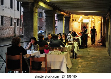 VENICE - APRIL 30 2011:People dinning in Italian restaurant in St Mark's Square, Venice Italy.Each year the town receives 18 million tourists. This equates to approximately 50,000 visitors each day