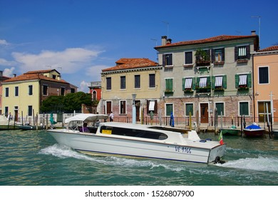 VENICE - AUG 11, 2018 - Motorboat taxi and buildings along the canals of Venice, Italy