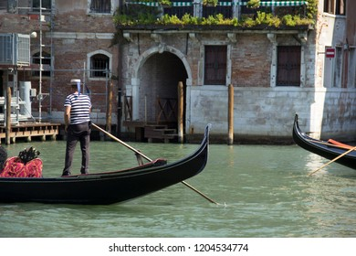 Venice - August 27: Gondolier drives a gondola with tourists on board on the Grand Canal on August 27, 2018 in Venice, Italy