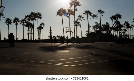 A Venice beach basketball court in silhouette.