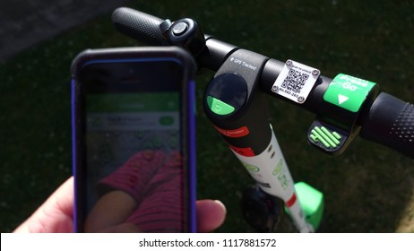 Venice Beach, CA / USA - June 15, 2018: Close up of handlebars and scan symbol of a lime-S electric scooter and hand holding mobile phone with open lime bike app