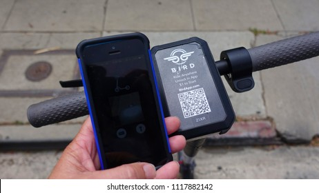 Venice Beach, CA / USA - June 16, 2018: Close up of handle bars of a dockless electric BIRD scooter with hand holding mobile phone with app open, ready to scan and unlock