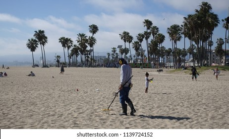 Venice Beach, CA / USA - June 3, 2018: A man searches the beach with a metal detector