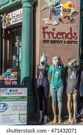 Venice Beach, California, USA - July 22, 2016: Three female mannequins wearing masks - two dogs and one unicorn stand in front of Friends Pet Supply and Gifts at the Venice Beach Boardwalk.