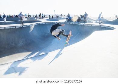 Venice Beach, Los Angeles, California - February 25 2018: Skater jumping at halfpipe with backlight at Venice Beach skatepark at a sunny day