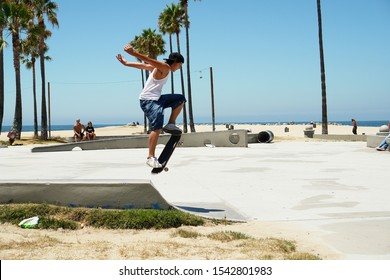 Venice Beach, Los Angeles, California / USA - 06/23/2007: Skateboarder jumping with his skateboard attempting a trick with his skate