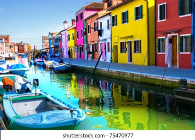 Venice, Burano island canal, small colored houses and the boat