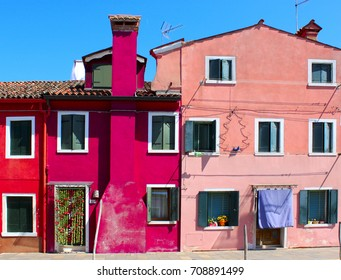 VENICE, BURANO ISLAND, ITALY - Summer, July 2017: Colorful houses with old green wooden shutters.
