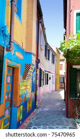 Venice, Burano island narrow street with small colored houses,  Italy