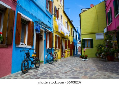 Venice, Burano island street with small colored houses and two bicycles,  Italy