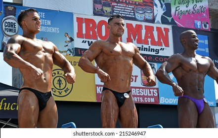 VENICE, CA SEPTEMBER 1, 2014:  Three bodybuilders stand in a line posing and flexing muscles at the Muscle Beach Championship bodybuilding competition on September 1, 2014 at Venice Beach, CA.