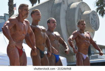 VENICE, CA SEPTEMBER 1, 2014:  Four bodybuilders stand in a line posing and flexing muscles at the Muscle Beach Championship bodybuilding competition on September 1, 2014 at Venice Beach, CA.