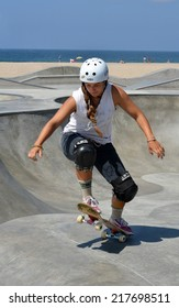 VENICE, CA - SEPTEMBER 1, 2014: A young girl wearing a helmet and knee pads raises the front end of her skateboard as she rides at the Venice Skate Park in Venice, California on September 1, 2014.