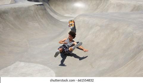 VENICE, CALIFORNIA - April 20, 2017: Skateboarder Brian Waters falling after attempting tricks at the Venice Skate Park in Venice Beach, California.