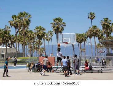 VENICE, CALIFORNIA - April 20, 2017: An group of unknown men playing basketball on an outdoor court in Venice Beach, California.