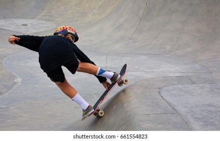 VENICE, CALIFORNIA - May 24, 2017: An unidentified young skateboarder doing tricks at the Venice Skate Park in Venice Beach, California.