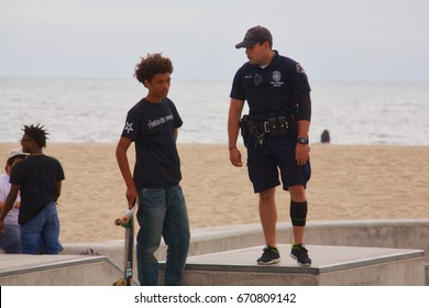 VENICE, CALIFORNIA - May 24, 2017: LAPD officer interacting with skateboarders at Venice Skate Park in Venice Beach California.