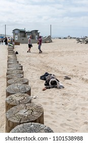 Venice, California, USA - May 27, 2018: Homeless man sleeping at Venice beach. Venice is a buzzing beach town with upscale commercial and residential pockets.