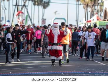 Venice, California/USA - December 15, 2018: Man dressed in Santa Claus costume greets runners at finish line of the Santa Monica - Venice Christmas 10K & 5K Run.
