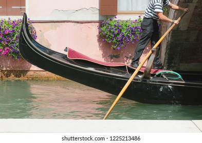 Venice canal, channel and gondolier rowing under the little bridge, small window with flowers