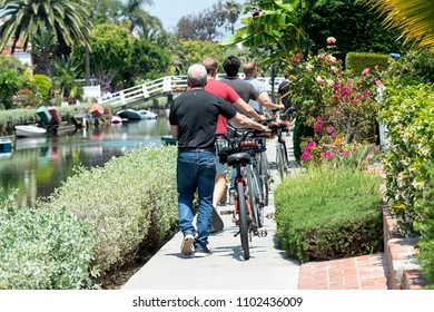 Venice Canal Historic District, CA - May 27, 2018: bike riders at the Venice Canal Historic District. It is a district in the Venice section of Los Angeles, California.
