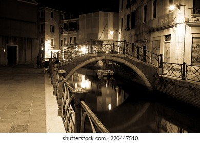 Venice canal late at night with street light illuminating bridge and houses