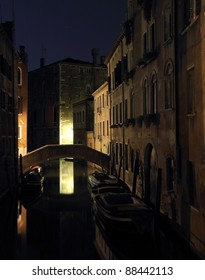 Venice canal at night in low light with boats and bridge