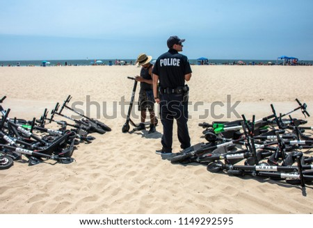 Venice, CA/USA - August 4, 2018: An LAPD officer waits to tell people riding electric scooters that the scooters are no longer allowed on the beachfront bike path.