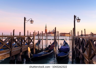 Venice with famous gondolas  in lagoon at sunrise as a background  can see the chucrh of San Giorgio Maggiore