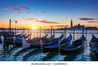 Venice with famous gondolas at sunrise, Italy. Gondolas in lagoon of Venice on sunrise, Italy. Venice with gondolas on Grand Canal against San Giorgio Maggiore church.