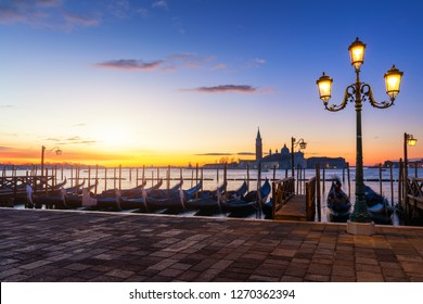 Venice with famous gondolas at sunrise, Italy. Gondolas in lagoon of Venice on sunrise, Italy. Venice with gondolas on Grand Canal against San Giorgio Maggiore church.
