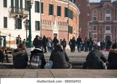 VENICE - February 19, 2017: People sit on the floor of venetian promenade La Riva degli Schiavoni