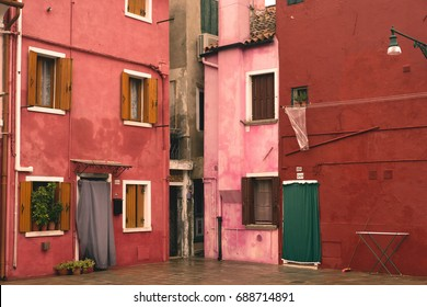 VENICE, FEBRUARY 2016: Buildings in different shades of red in a corner of Burano, Venice