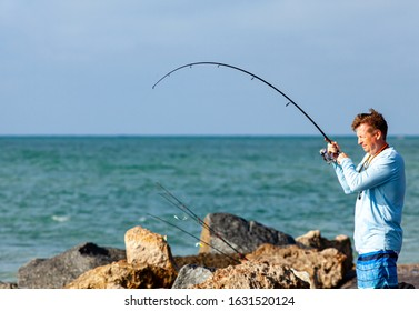 Venice FL circa October 2019 A fisherman reels in a freshly caught fish at the Venice FL jetty. The fishing rod is bent over due to the weight of the fish.