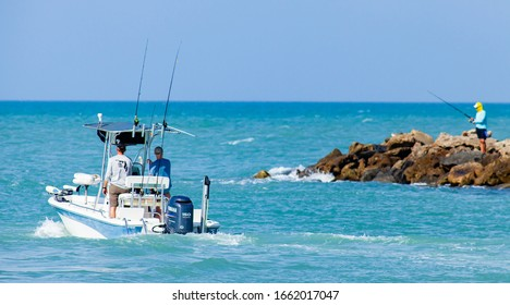 Venice FL February 25 2020 A small center console fishing boat with two fishermen heads out in to the Gulf of Mexico while a lone fisherman fishes from  the rocks of the Venice (FL) jetty.