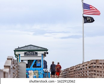 Venice FL January 19 2019 An image of two older male friends walking out on the Venice (FL) municipal fishing pier. The bait shop is shown on the left, and the US and POW flags are on the right.