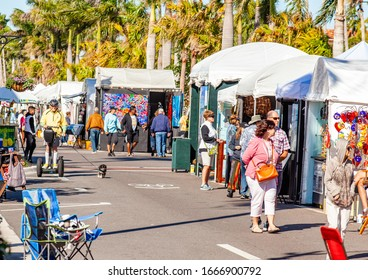 Venice FL March 7 2020 Tourists stroll through the Venice (FL) Arts & Crafts Festival on a sunny day. Multiple vendors with pop-up canopies are seen